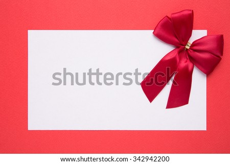 Blank Christmas card or invitation with bow on red background - stock photo