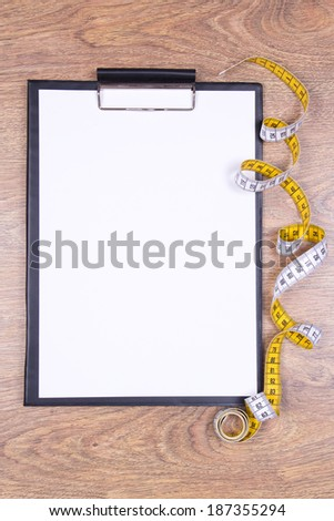 blank clipboard and measure tape on wooden table - stock photo