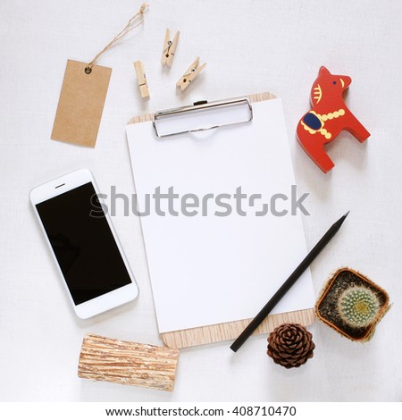 Blank clipboard and smartphone with cute decorated on workspace desk - stock photo