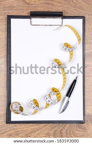 blank clipboard, pen and measure tape on wooden table - stock photo