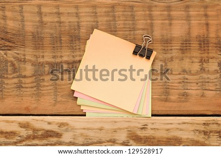 blank color stickers and paper clips on wooden table