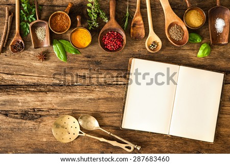 Blank cookbook and spices on wooden table - stock photo