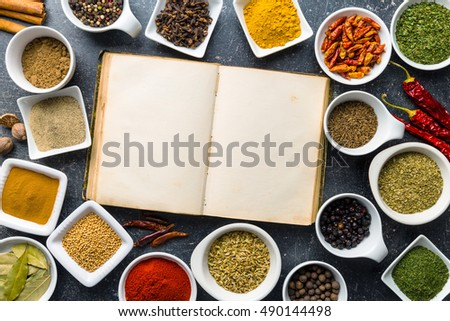 Blank cookbook and variuos spices and herbs. Top view.