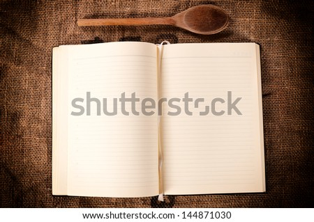 Blank cookbook and wooden ladle on abstract background - stock photo