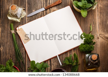 Blank cookbook for recipes with herbs - stock photo