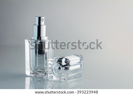 blank cosmetic bottle with silver cap on white background - stock photo