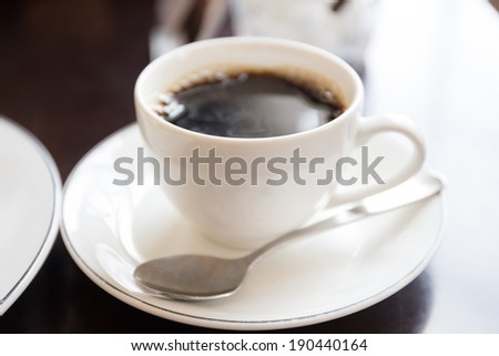 blank cup of coffee with steam, selective focus at the front of the cup for your text or logo - stock photo