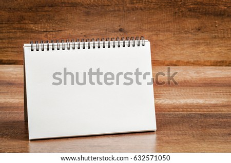 Blank diary note on wooden background.