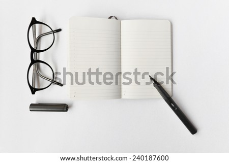 Blank diary, pen, and glasses on white background
