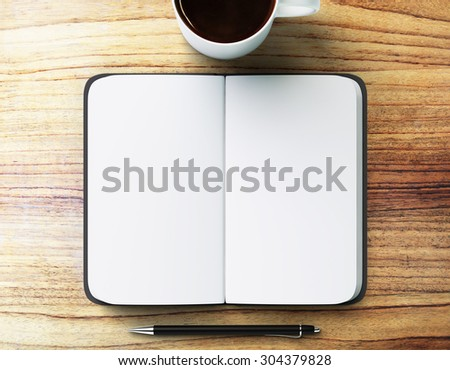 blank diary with pen and cup of coffee on a wooden table - stock photo
