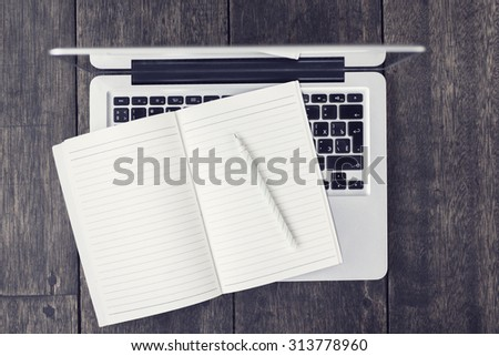 Blank diary with pen with laptop on a wooden table - stock photo