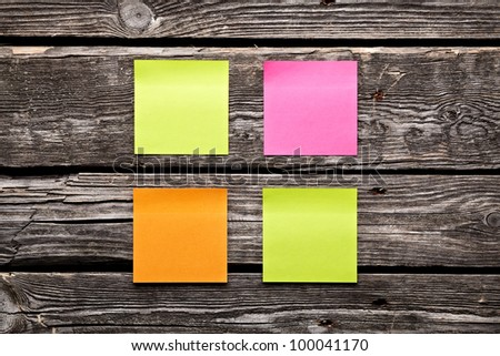 Blank different colors sticky note paper sheets. Closeup on old vintage wooden table. - stock photo