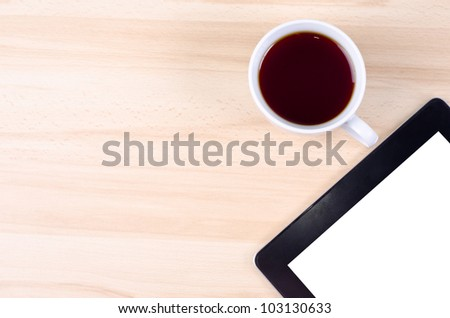 Blank digital black tablet on a desk with empty empty white screen and cup of coffee