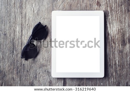 Blank digital tablet on a wooden table with sunglasses - stock photo