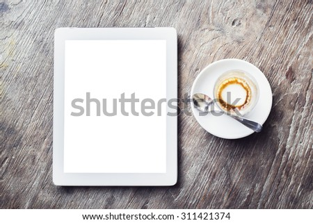 Blank digital tablet with cup of coffee on a wooden table, mock up - stock photo