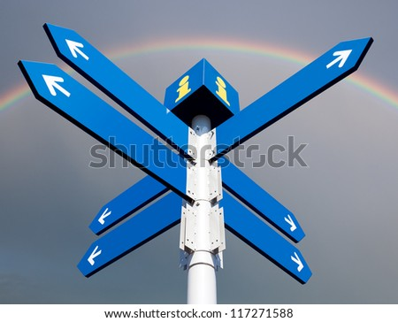 Blank directional road signs on rainbow background - stock photo
