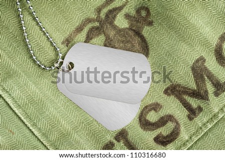 Blank dog tags on an old military uniform from the 1960's. Room for copy on the dog tags.