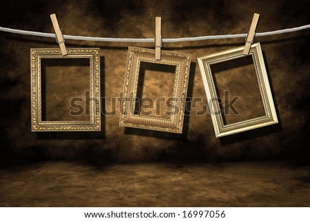 Blank Empty Gold Photo Frames on a Distressed Grunge Background Hanging on a Rope - stock photo