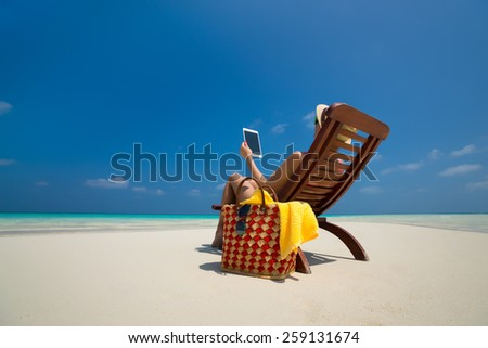 Blank empty tablet computer in the hands of women on the beach - stock photo