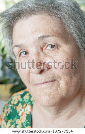 Blank expression closeup face senior woman. Indoors - stock photo
