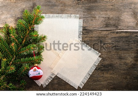 Blank fabric with space for text decorated with branch of christmas tree at wooden background