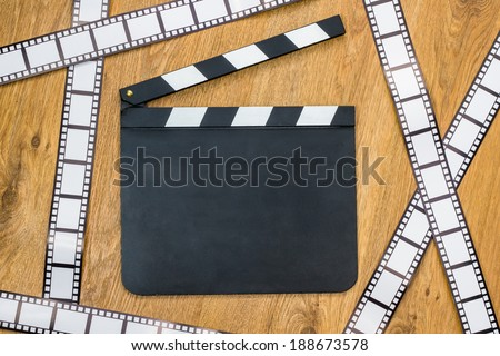 Blank film slate and film stripes on a wooden background - stock photo