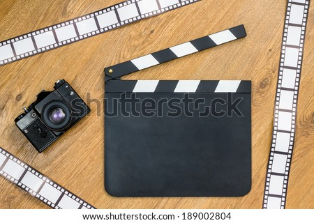 Blank film slate, vintage camera and film strips with copy space against wooden background  - stock photo