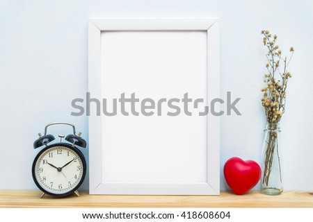 Blank frame, alarm clock and heart on the table, mock up