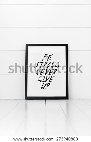 Blank frame on a white background with quotation. Be strong never give up - stock photo