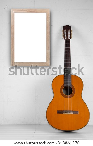 Blank frame with Spanish guitar in room as background