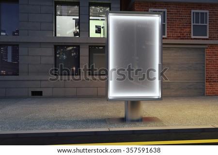 Blank glowing billboard on empty street at night, mock up - stock photo