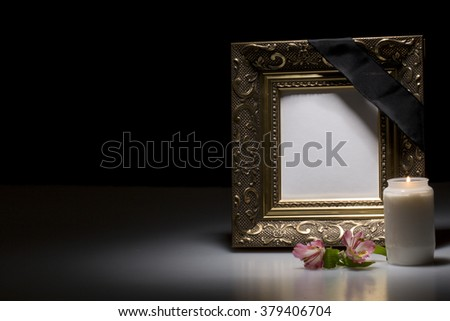 blank golden mourning frame with flower and candle on dark background - stock photo