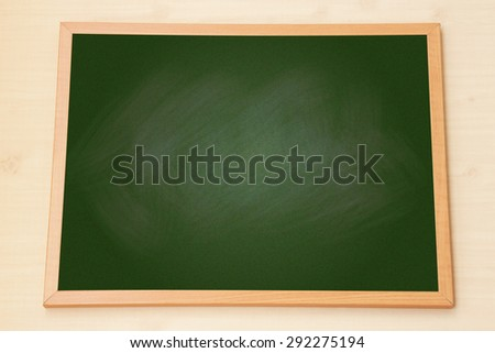 Blank green chalkboard with wooden frame on wood background.