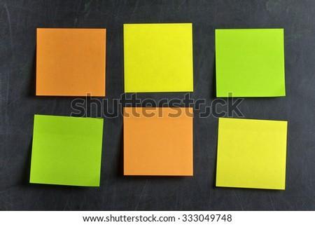 Blank Green orange and yellow postits glued on blackboard or chalkboard - stock photo
