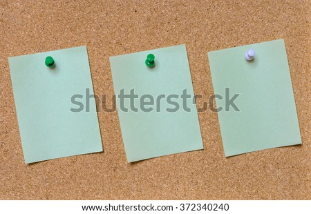 Blank green paper posted on cork board with tack pin for text and background
