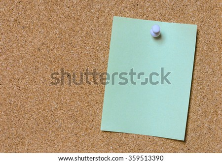 Blank green paper posted on cork board with white tack pin for text and background