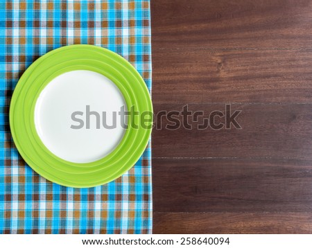 Blank green plate on checked tablecloth over wooden table background - stock photo