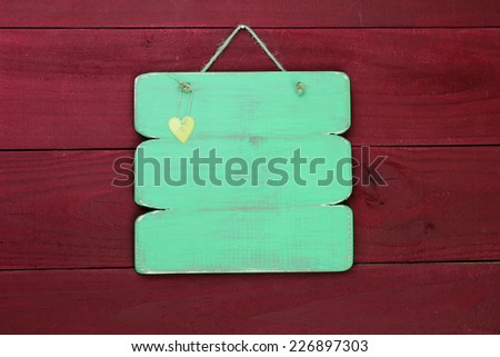 Blank green sign with gold heart hanging on antique red old weathered wood background