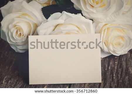 Blank greeting card and white artificial rose on old wooden table with vintage and vignette tone