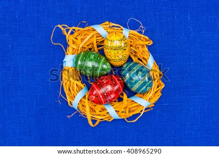 Blank, greeting easter card with handmade easter eggs in nest in textile blue background - stock photo