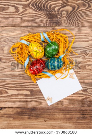 Blank, greeting easter card with handmade easter eggs, nest in wooden background.Place for text - stock photo