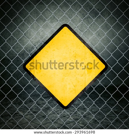 Blank Grunge Yellow Warning Sign on Chain link Fence of Industrial Warehouse as Copy Space for Your Message. - stock photo