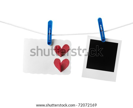 Blank handmade card and blank instant photo frame hanging on the clothesline. Isolated on white background. - stock photo