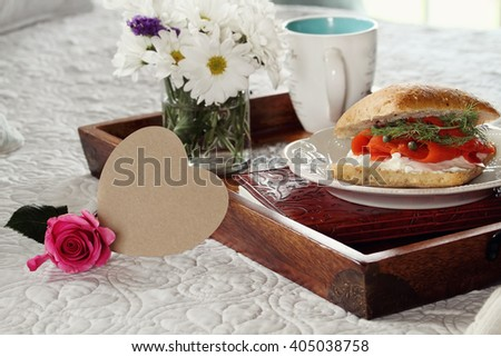Blank heart shaped card and flowers with breakfast served in bed. Extreme shallow depth of field with selective focus on heart. - stock photo