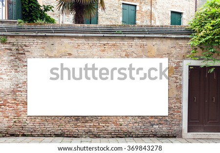 Blank horizontally oriented billboard with copy space on the wall in Venice, Italy. Passenger in motion blur is also seen  - stock photo