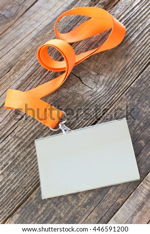 Blank  ID card tag with ribbon on wooden background - stock photo