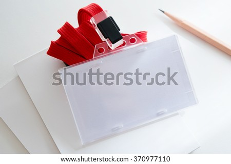 Blank ID or security card on office table, with red neck strap. - stock photo