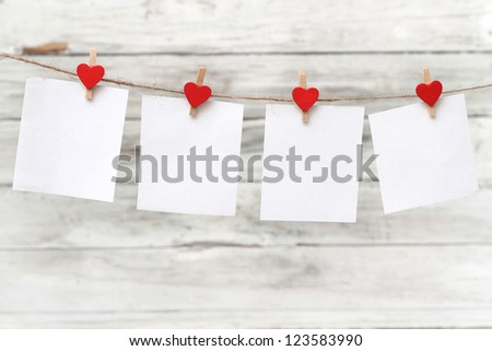 blank instant paper hanging on the clothesline on wooden background - stock photo