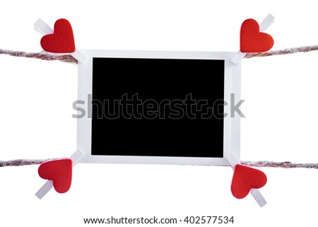 Blank instant photo and clippaper heart hanging on the clothesline on white background.Designer concept. - stock photo