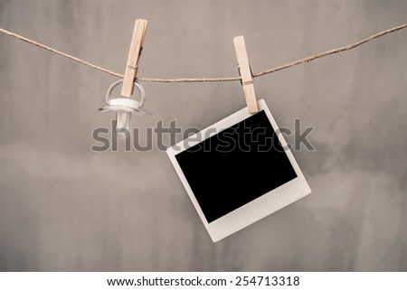 blank instant photo and pacifier hanging on the clothesline - stock photo